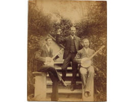Photograph of two Banjo players seated on outdoor staircase, with another man standing playing the castanets.